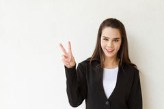 Woman business executive showing 2 or two fingers hand gesture. On plain background Royalty Free Stock Images