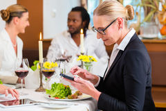 Woman on business lunch checking mails on phone Stock Photos