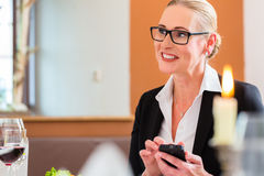 Woman on business lunch checking mails on phone Royalty Free Stock Photography