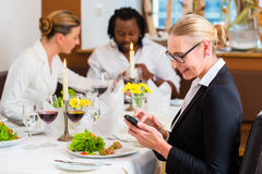 Woman on business lunch checking mails on phone Royalty Free Stock Image