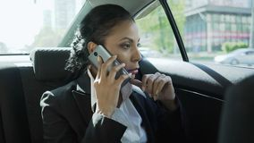 Woman in business suit on back seat of car, having conversation on phone, stress. Stock footage stock video