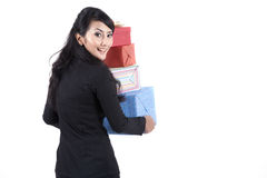 Woman in business suit with Christmas Gifts. Professional worker carrying stack of christmas gifts isolated over white Royalty Free Stock Photo