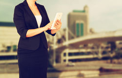 Woman in business suit on a city building background. filtered image Stock Photos