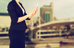 Woman in business suit on a city building background. filtered image. Stock Image