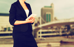 Woman in business suit on a city building background. filtered image Royalty Free Stock Photos