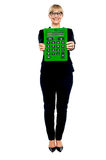 Woman in business suit displaying large green calculator. Full length studio shot vector illustration