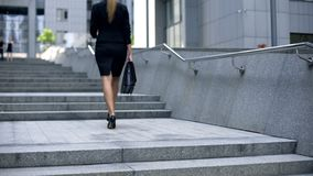 Woman in business suit going upstairs, climbing career ladder, achieving goals. Stock photo royalty free stock photo