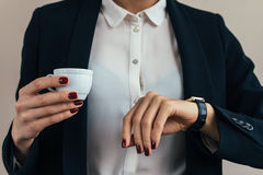 Woman in a business suit holding a cup of coffee and checks the Stock Image