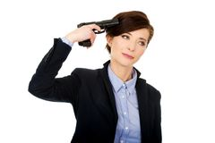 Woman in business suit holding a gun. Royalty Free Stock Photography