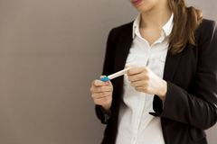 Woman in a business suit looking at positive pregnancy test. Sto Stock Image
