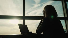 A woman in a business suit looks out the window of her office. Concept - look ahead in business