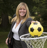 Woman in business suit and netball net scoring a goal Royalty Free Stock Image