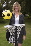 Woman in business suit and netball net scoring a goal Stock Images