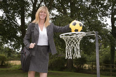 Woman in business suit and netball net scoring a goal Royalty Free Stock Photography