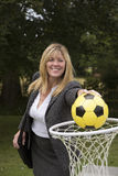 Woman in business suit and netball net scoring a goal Stock Photography
