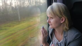 A woman in a business suit rides a train, looks out the window. Business woman is going by train, looking out the window at the spring landscape. 4K video stock footage