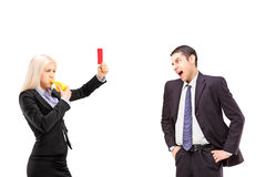 Woman in business suit showing a red card to an angry man in a s Stock Images