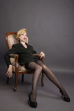 Woman in a business suit sits in an armchair Royalty Free Stock Image