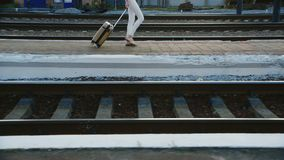 A woman in a business suit in a travel bag is on the railway station. In the picture can be seen only the legs and a bag. On wheels stock video