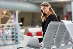 Woman on business trip with laptop and smartphone stock photo