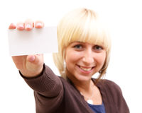 Woman with businesscard. A smiling woman shows a white businesscard to us Stock Photo