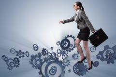 The woman businessman climbing cogwheels Royalty Free Stock Image