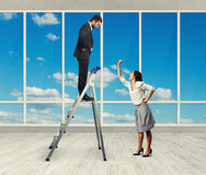Woman and businessman on stepladder Stock Image