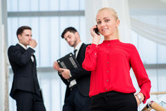 Woman Businessman talking on a mobile phone. Young businessman s. Tanding on the steps and keeps his hands in his pockets while her parnery talk to each other Stock Photos