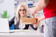 The woman businesswoman receiving mail parcel from courier. Woman businesswoman receiving mail parcel from courier Royalty Free Stock Image
