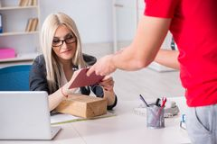The woman businesswoman receiving mail parcel from courier. Woman businesswoman receiving mail parcel from courier stock photo