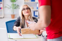 The woman businesswoman receiving mail parcel from courier. Woman businesswoman receiving mail parcel from courier royalty free stock images