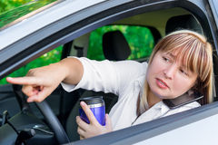 Woman with busy hands driving shows forward Stock Photo