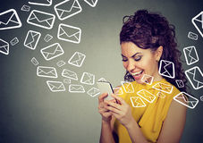 Woman busy sending messages on smart phone email icons flying out. Happy woman busy sending messages on smart phone email icons flying out of cellphone isolated Stock Photography
