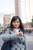 Woman on busy street. Young Asian woman checking her watch on a street in a large city Stock Photos