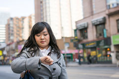 Woman on busy street. Young Asian woman checking her watch on a street in a large city Royalty Free Stock Photo