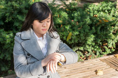 Woman on busy street. Young Asian woman checking her watch on a street in a large city Royalty Free Stock Image