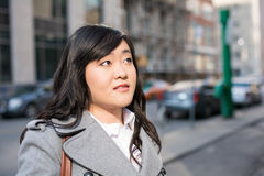 Woman on busy street. Young Asian woman in coat on a street in a large city Stock Images