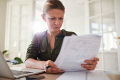 Woman busy working at home office. Portrait of young female sitting at table reading documents. Woman busy working at home office royalty free stock photography