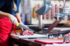 Woman in butcher shop selling meat fillet Royalty Free Stock Image