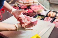 Woman in butcher shop selling meat fillet stock images