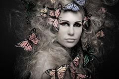 Woman with butterfly in big curly hair on black.