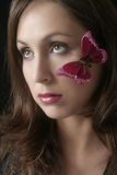 Woman with butterfly on her cheek Royalty Free Stock Photos
