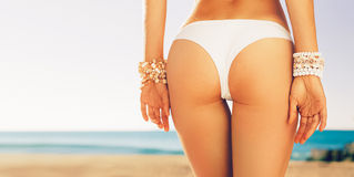Woman buttocks slim figure, beach accessories, bracelets Stock Photography