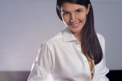 Woman buttoning her shirt while dressing Royalty Free Stock Photography