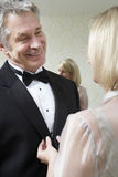 Woman Buttoning Husband's Tuxedo Jacket Stock Images