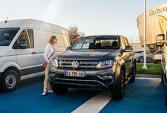 Woman buy new Volkswagen Amarok - pickup truck. Strasbourg, France - Oct 15, 2017: Young woman buy looking at the special offer at the car dealership showroom stock photo