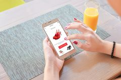 Woman buy red shoes online . Mobile app or web site on screen. Table and juice in background royalty free stock photo