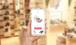 Woman buy shoes online with modern mobile app. Shoe store in background royalty free stock photos