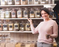 Woman buyer selects herbs in store of ecological products. Ordinary woman buyer selects herbs in store of ecological products Royalty Free Stock Photo