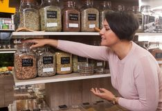 Woman buyer selects herbs in store of ecological products. Ordinary woman buyer selects herbs in store of ecological products Royalty Free Stock Image